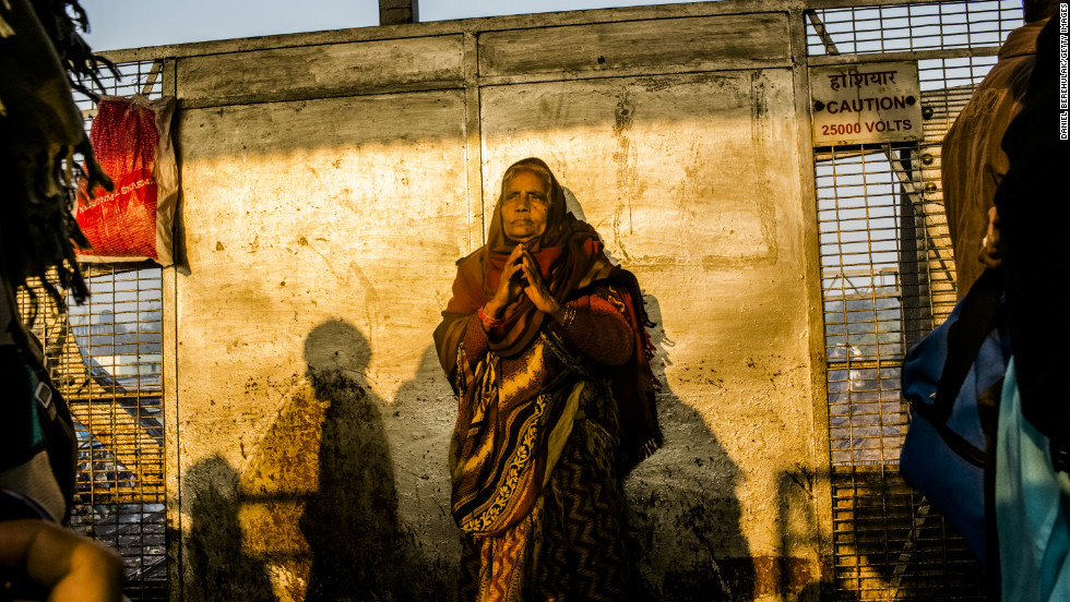 A Hindu devotee clasps her hands together as she waits for her train as people move through Allahabad train station.