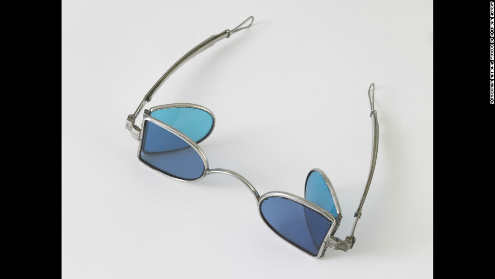 "In the 19th century, people wore these kinds of glasses, called ""eye protectors"" or ""railroad glasses."" This pair, from 1850, has steel frames with four colored lenses. They were meant to protect weak eyes from bright light, dust and wind while riding or driving. The lenses are tinted with shades of blue and blue-green, although other lenses could also be amber and gray."