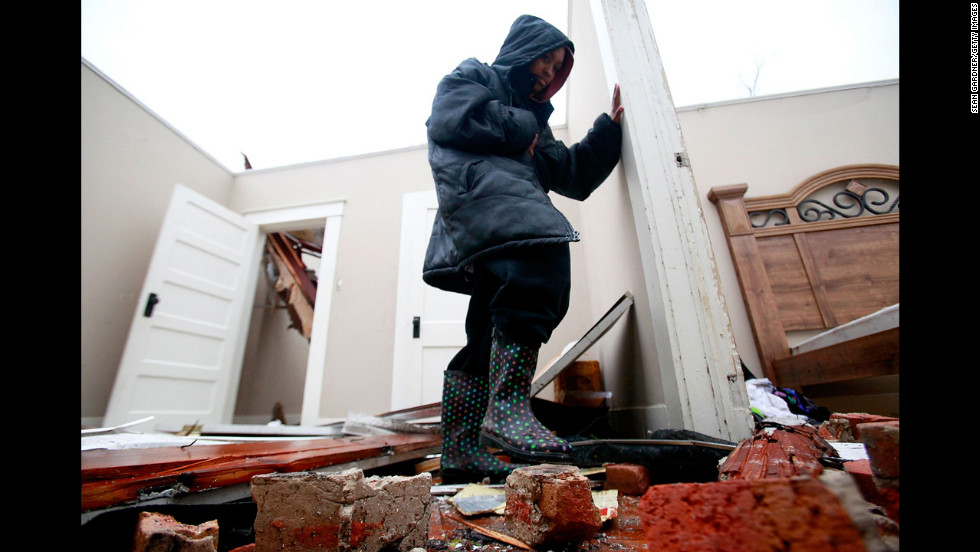 Crystal Hamilton steps over rubble in her living room in Hattiesburg on February 11.