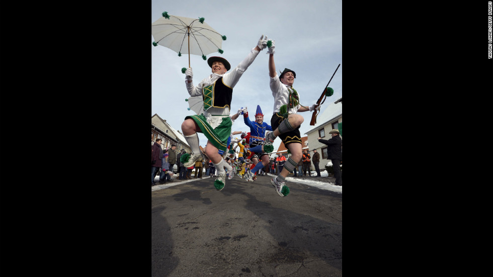 People jump about at the Springerzug carnival parade,.