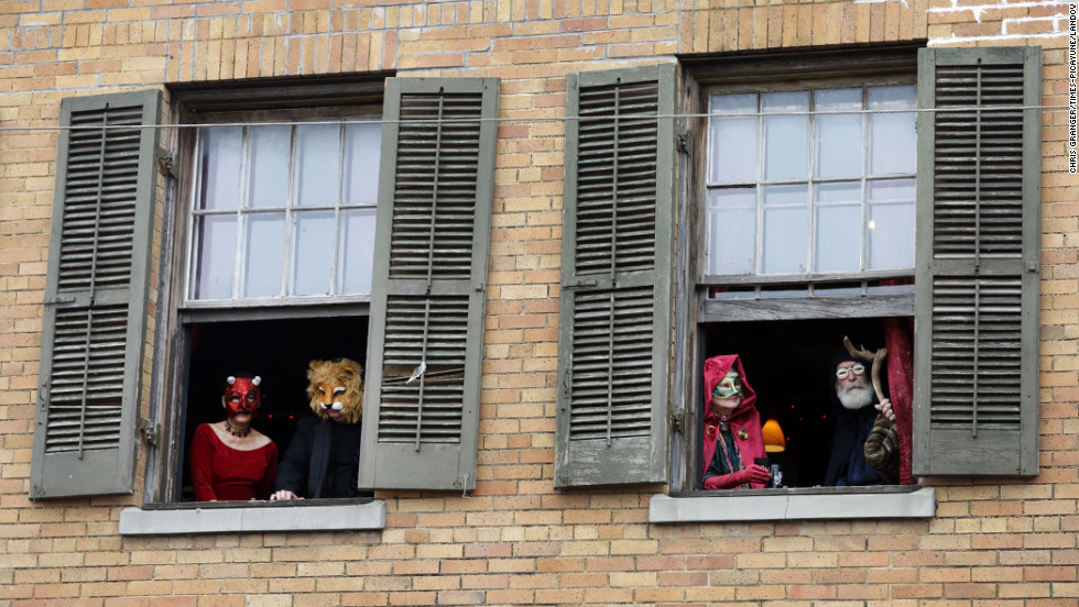 Revelers in costume watch from a window at Mimi's bar as people gather on the street below.