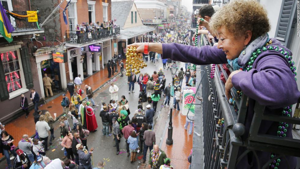 A reveler dangles beads off a balcony on Bourbon Street.
