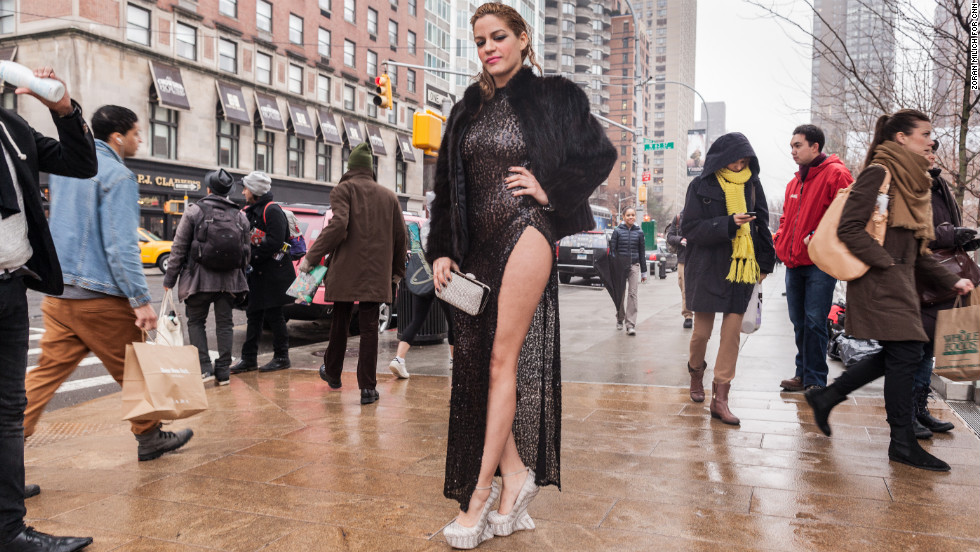 Artist Patricia Mota wears a coat while braving the cold weather in a long slitted dress on February 11.