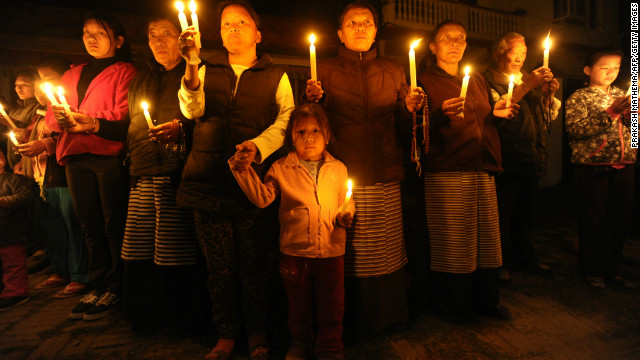Tibetans-in-exile hold a candlelight vigil following the self-immolation attempt by a monk in Kathmandu on February 13, 2013.