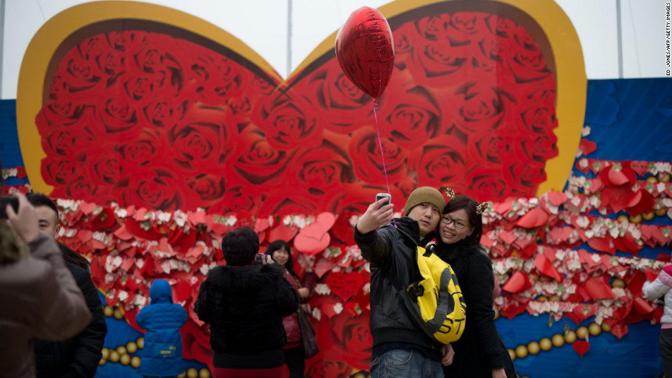 A couple stands in front of a heart-shaped backdrop for a self-portrait at a park in Beijing.