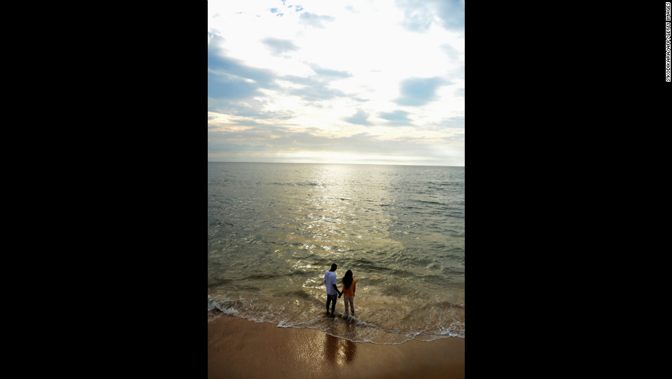 A couple stands on the Galle Face beach in Colombo, Sri Lanka.