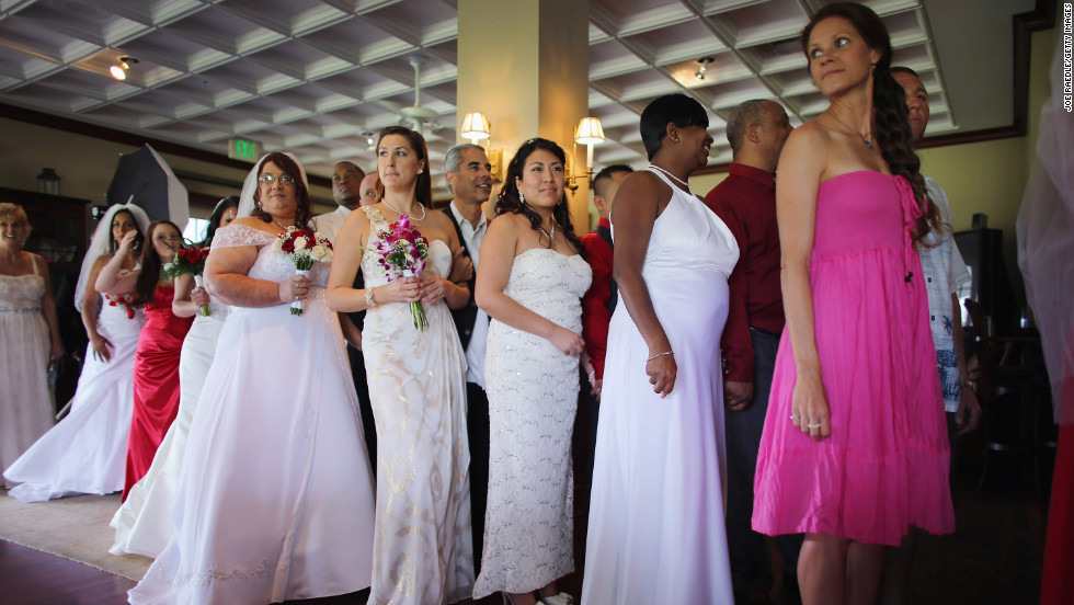 Brides line up with their husbands-to-be during a group Valentine's Day wedding at the National Croquet Center on Thursday, February 14, in West Palm Beach, Florida. About 40 couples tied the knot.
