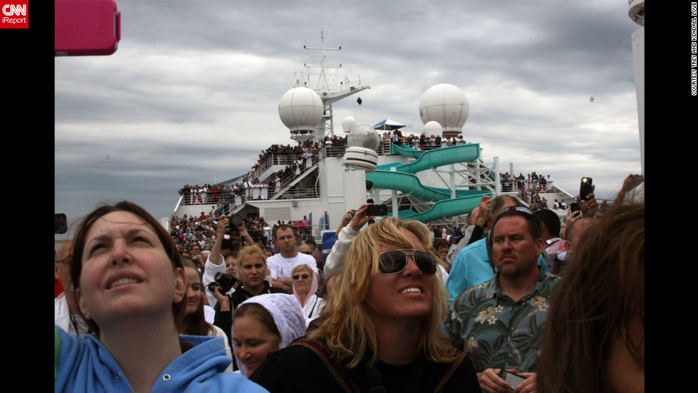 Passengers fill the deck of the ship and look up toward the sky.