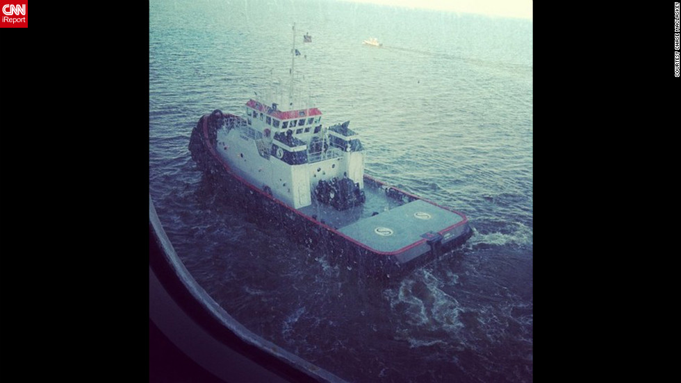 """One of two tugboats pulling us through the channel to Mobile, Alabama, along with a channel guide boat,"" writes Maclaskey. The ship is being towed slowly to Mobile, Alabama, and is expected to port late February 14."
