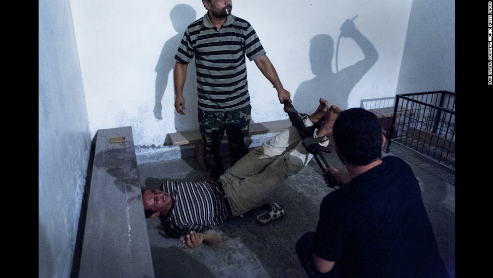 <strong>Second prize -- spot news single:</strong><br />Syrian opposition fighters interrogate captured government informants on July 31, 2012, in Aleppo, Syria, in a photograph by Emin Ozmen. The informants were declared guilty and tortured throughout the night, according to Ozmen.