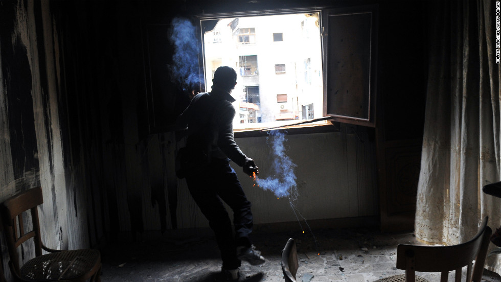 A rebel fighter throws a home-made grenade at Syrian government forces in Aleppo on February 16.