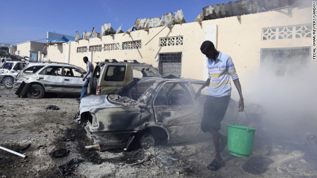 A man carries a bucket of water at the scene of an explosion in Mogadishu, Somalia, on Saturday, February 16.