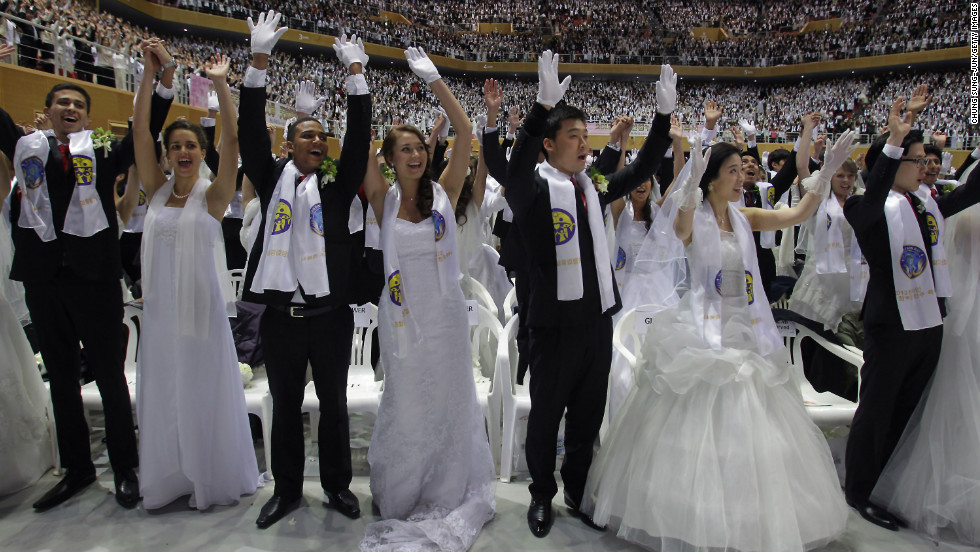 Couples cheer during the wedding ceremony.