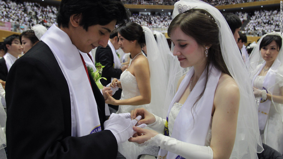 A bride puts a ring on her groom's hand.
