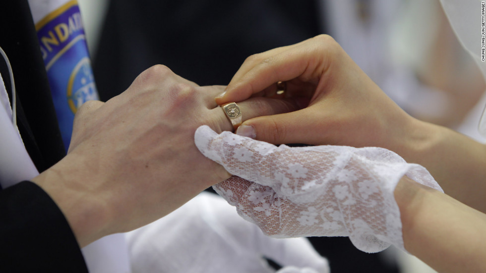 Couples exchange their wedding rings.