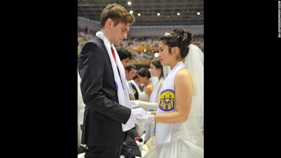 Newly married couples hold hands to pray.