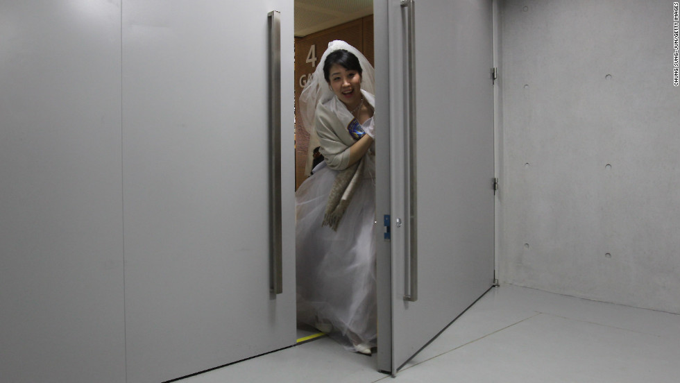 A bride passes through a door at the center.