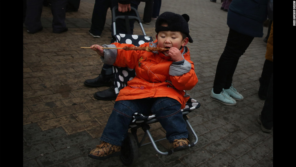 A  boy eats a mutton skewer at a Spring Festival Temple Fair on February 11 in Beijing.