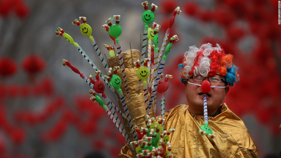 A vendor dressed as a clown at a Spring Festival Temple Fair in Beijing shows off his toys for sale on February 11.