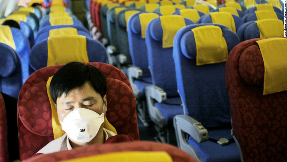 A masked passenger sleeps on an nearly empty Dragonair flight from Hong Kong to Beijing on May 21, 2003. The Hong Kong-based carrier saw passenger volumes plummet after the SARS outbreak.