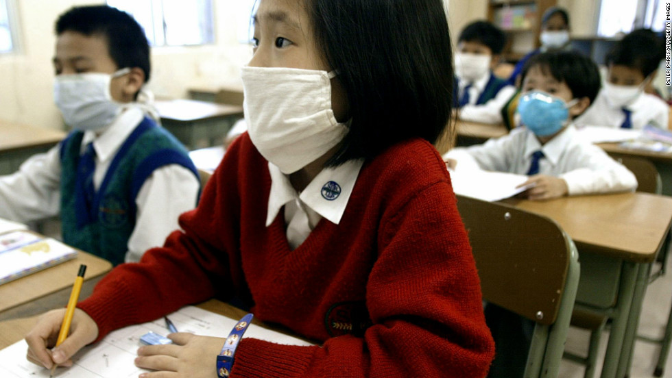 Hong Kong schoolchildren wear masks in their classroom, March 28, 2003.