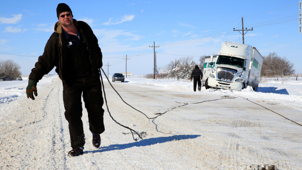 Tow truck driver Tyson House helps trucker Gary Wheeler of Kansas City on Friday, February 22, in Greensburg, Kansas, after his truck slid off the road. The huge snowstorm was moving across the Plains on Thursday.