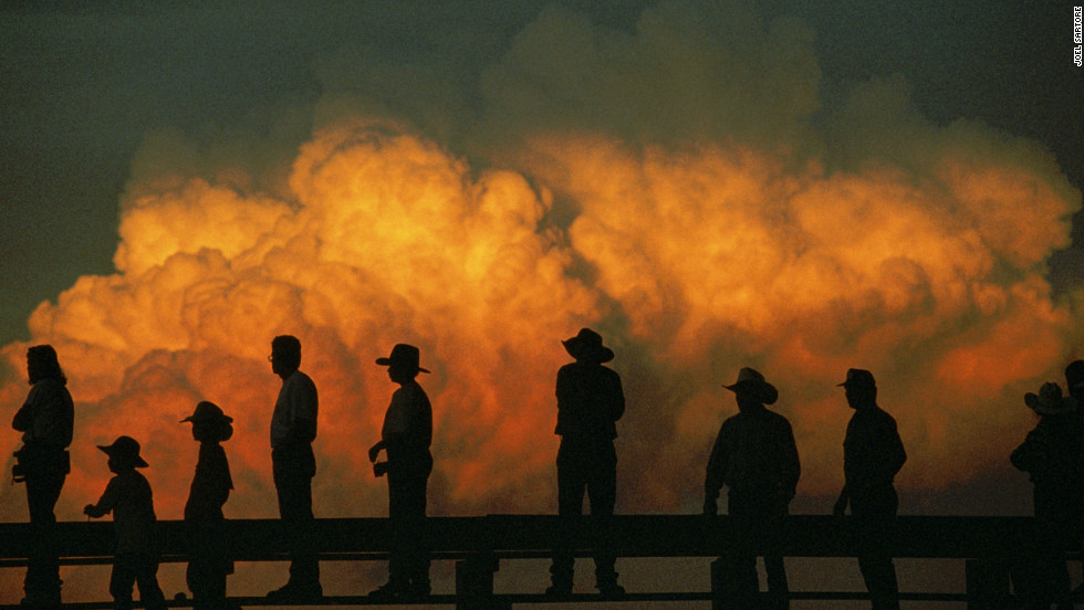 Silhouetted at sunset against a radiant cumulus cloud, spectators take in the action at Nebraska's Big Rodeo, held annually in Burwell since 1921.