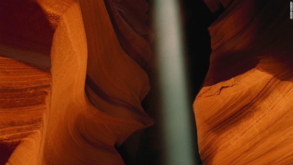 A shaft of light bisects the distinctive Navajo Sandstone shapes of Antelope Canyon, a slot canyon near Page formed by millennia of flash flooding.