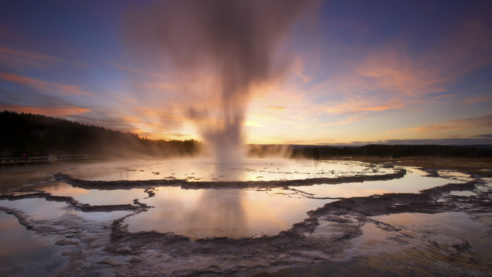 Back-lit against a painted sky, Yellowstone's Great Fountain Geyser shoots above the terraced reflective pools around its vent.