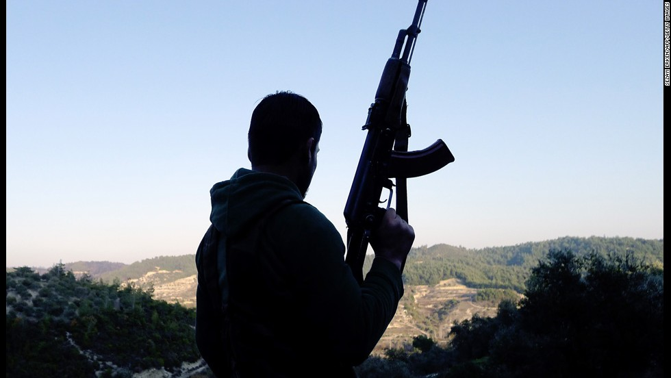 A member of the Free Syrian Army looks out over a valley in the village of Ain al-Baida on December 15, 2011.