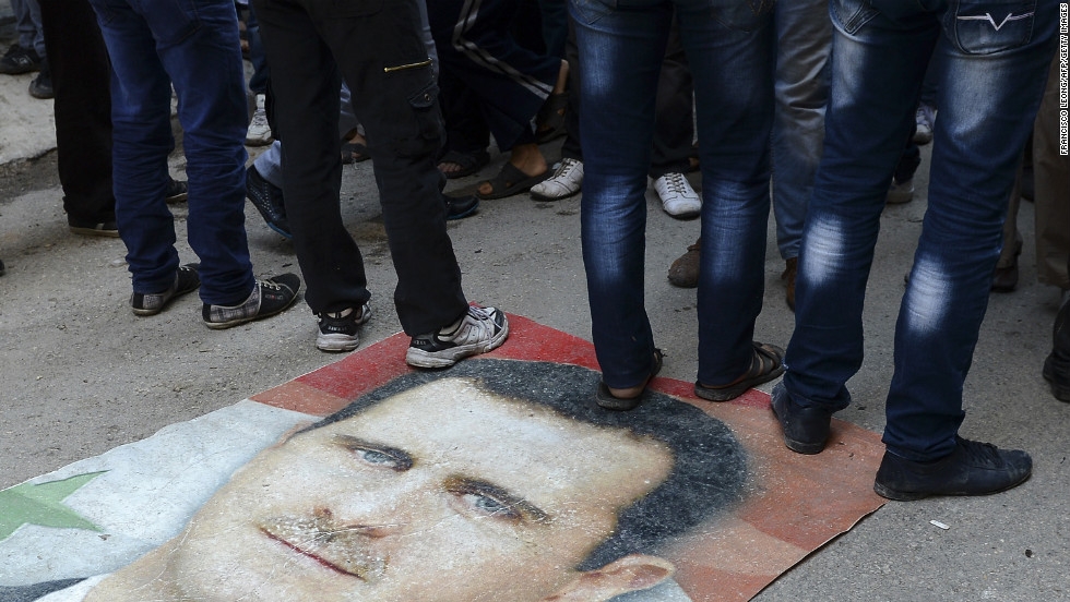 Syrians protesters stand on Assad's portrait during an anti-regime demonstration in Aleppo on November 16, 2012.