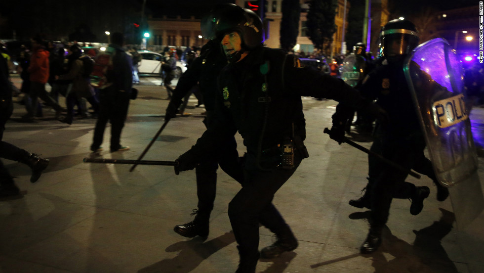 Spanish police in riot gear chase protesters.