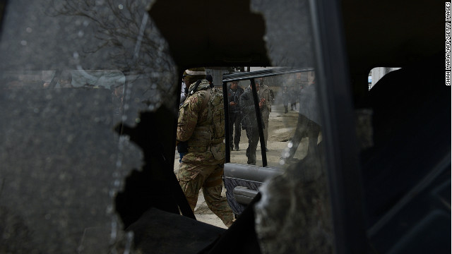 A US soldier and Afghan policemen are seen through the broken window of a suicide bombers' car in Kabul on February 24, 2013.