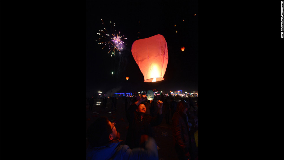 Chinese men release a paper lantern into the sky on the eve of the Lantern Festival on Saturday, February 23.