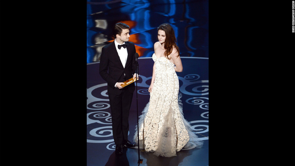 """Harry Potter's"" Daniel Radcliffe and ""Twilight's"" Kristen Stewart present the award for best production design. Stewart, who was photographed using crutches on the red carpet, had to limp to the microphone."