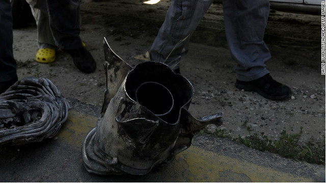 Israeli bomb technicians inspect the remains of a rocket fired from the Gaza Strip and near Ashkelon on Tuesday.