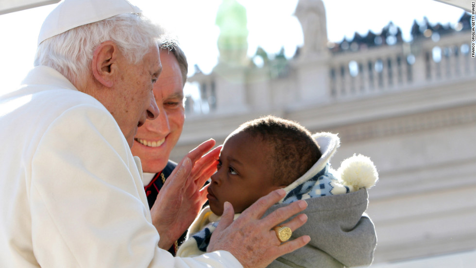 The pope kisses a child as he arrives.