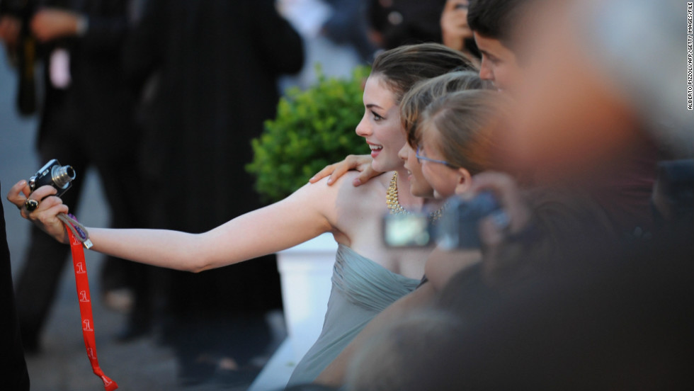 "Hathaway stops for a snapshot with fans before the screening of  ""Rachel Getting Married"" at the Venice International Film Festival in September 2008."
