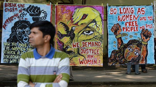 A demonstrator stands in front of posters during a protest rally in New Delhi calling for justice for women.