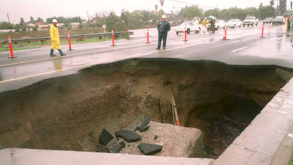 A 30-foot-deep sinkhole appeared in a busy street in a suburb east of downtown Los Angeles. A motorist drove into the hole but was rescued before a concrete slab fell onto the car.