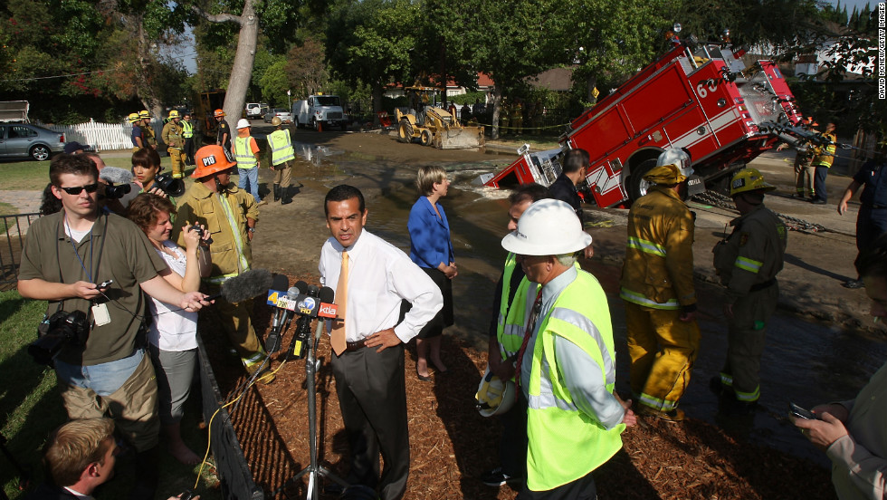 A fire truck protrudes from a sinkhole as Los Angeles Mayor Antonio Villaraigosa talks to reporters in September 2009.