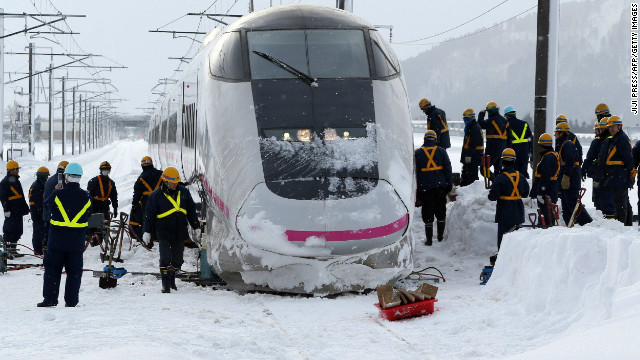 Railway workers inspect a bullet train Sunday after it derailed during its journey from Tokyo to northern Japan.