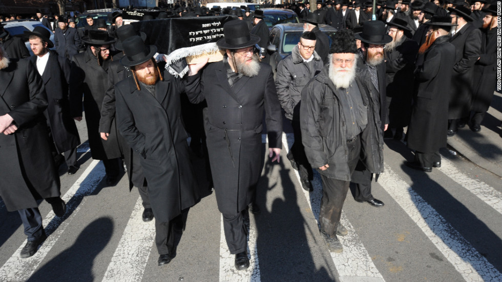 Men carry the coffins of the young couple through the streets of Williamsburg, Brooklyn, on Sunday.