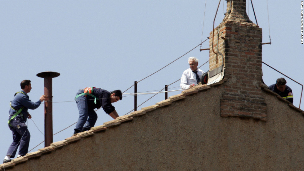 Vatican workers place a chimney pot on the roof of the Sistine Chapel for the conclave in April 2005 that ultimately elected Pope Benedict XVI. Onlookers focus on the chimney for smoke signals that indicate whether a new pope has been elected. Black signals no election yet; white means there's a new pope.