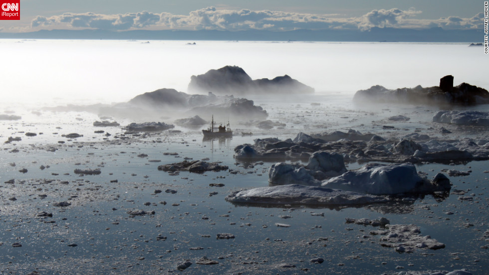 "A fishing boat winds through icebergs and fog on its way to port in Ilulissat, Greenland. ""It really was beautiful,"" <a href=""http://ireport.cnn.com/docs/DOC-832859"">Jeffrey Swensen</a> said. ""Piloting a boat through that ice seems to require a great deal of patience."""