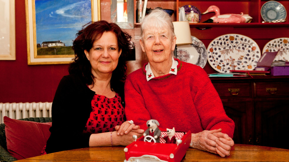 "Like mother, like daughter. Shirley Hughes and her daughter Clara Vulliamy together after working on their first collaboration, ""Dixie O'Day"". A model of Dixie and his sidekick Percy is in front of them on the table."