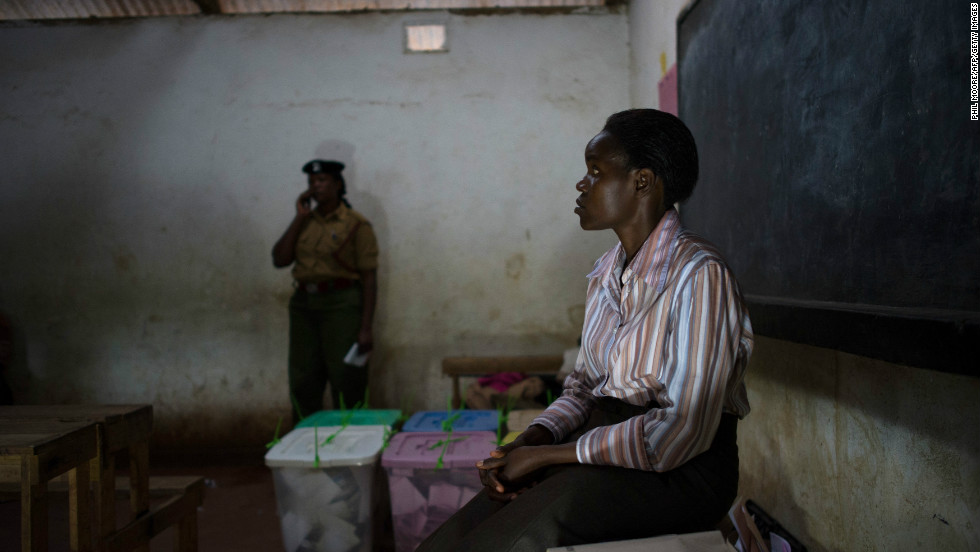 An election observer sits beside sealed ballot boxes after the close of voting at the Oloolua Primary School as voting closes.
