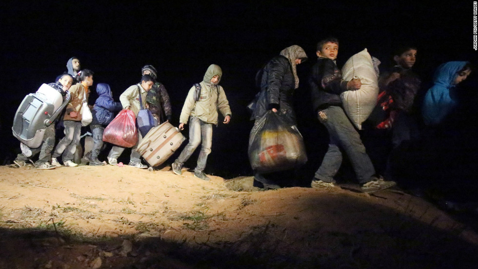 Refugees fleeing the conflict in Syria arrive at the Jordanian border in February 2013.