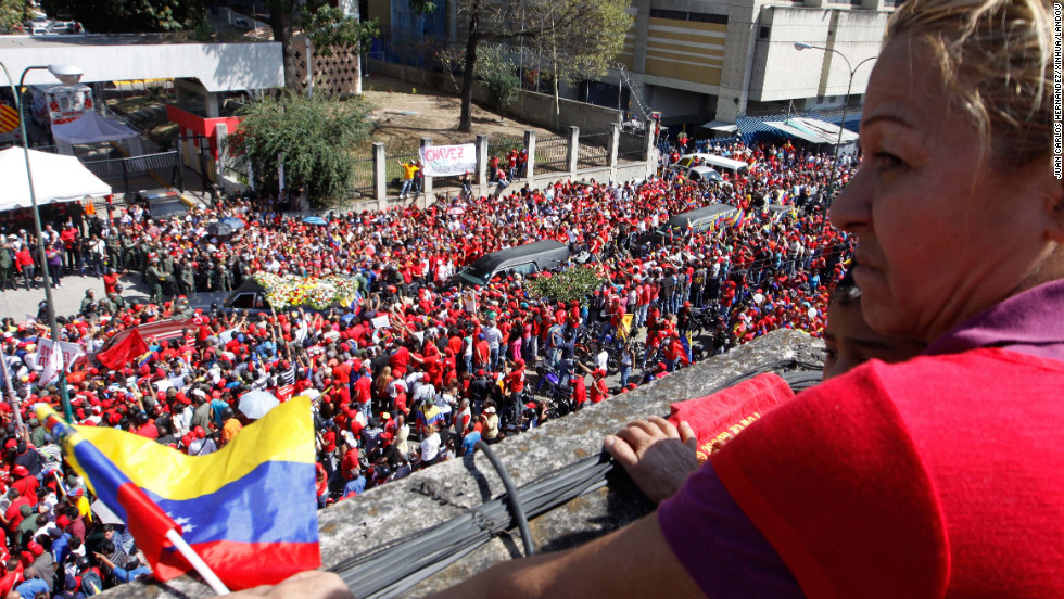 A woman watches as Chavez's casket is driven through the streets of Caracas on March 6.