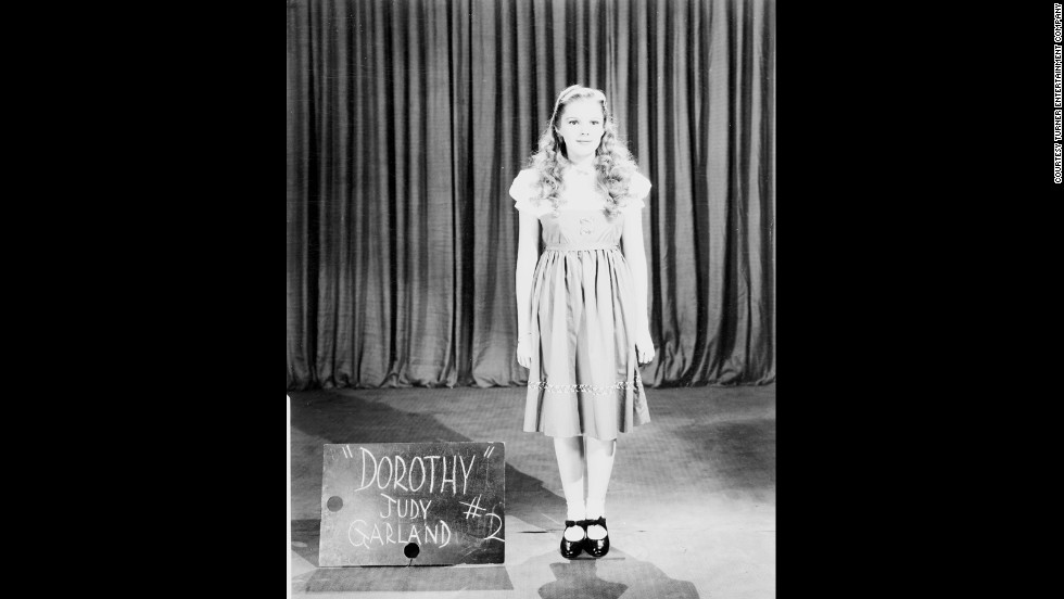 A wardrobe test shot of Judy Garland in a rejected Dorothy costume with a blonde wig.